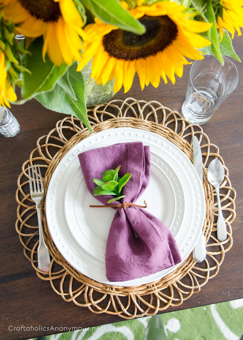 Beautiful Fall Place Setting idea with sunflowers and plum colored napkins