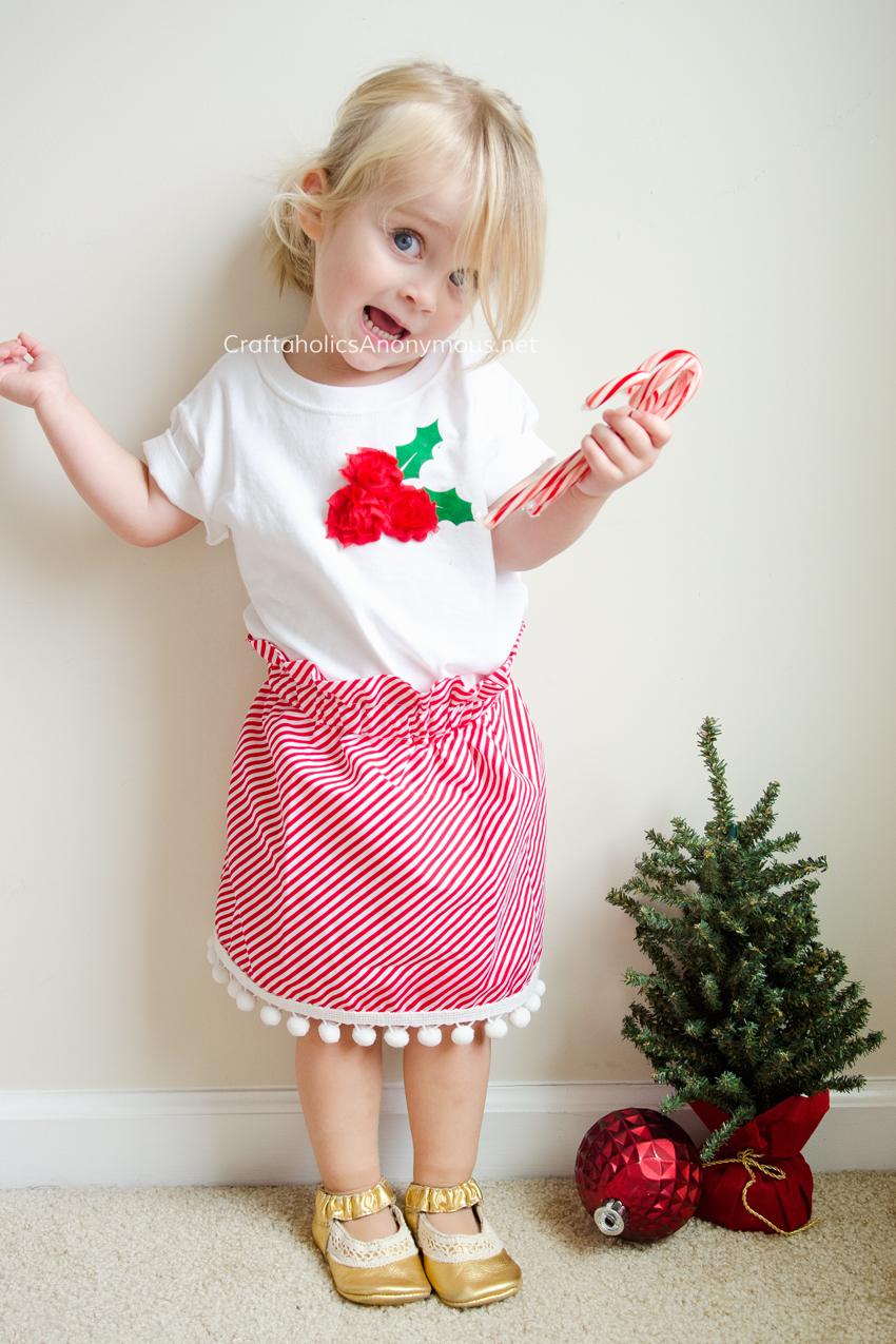 DIY Christmas outfit for girls. Holly Berry Shirt with Candy Cane stripe Skirt with Pom poms. Easy to make and ADORABLE! www.craftaholicsanonymous.net