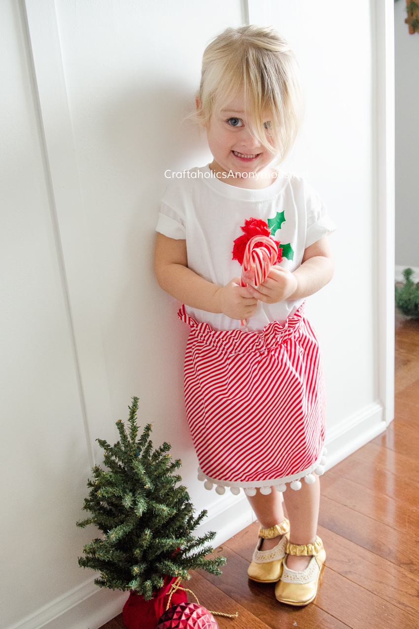 DIY Candy Cane Christmas skirt with paper bag waist and pompom trim. So adorable!! Whips up in about 1 hour. Free Easy sewing pattern! www.CraftaholicsAnonymous.net